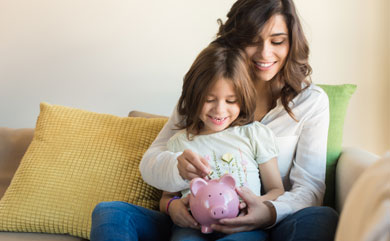 Picture of mom helping daughter put money in piggy bank